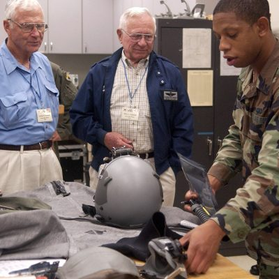 Senior Airman Cortney Tanner shows some of the life support equipment used by today's pilots to Korean War veterans Lt. Gen. Charles Cleveland (left) and Col. Wilbur Carpenter Sept. 11 at Kunsan Air Base, South Korea.  The veterans were visiting Kunsan and sharing their flying experiences with 8th Fighter Wing Airmen.  Airman Tanner is a life support journeyman with the 35th Fighter Squadron.  (U.S. Air Force photo/Senior Airman Giang Nguyen)