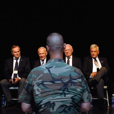 Retired Air Force members Lt. Gen. Charles G. Cleveland (from left), Maj. Gen. Carl G. Schneider, Col. Ralph Gibson, Col. Buzz Aldrin, Col. Pete Carpenter, Col. Ken Shealy, Col. Harold Fischer and Col. Robert Moxley, answer questions during an Air Force Call with nearly 150 Airmen from Yongsan Army Garrison, South Korea. (U.S. Air Force photo/Staff Sgt. Bennie J. Davis III)