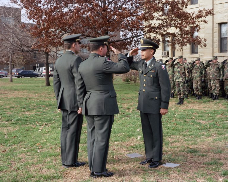 Captain (CPT) Jerry de la Cruz, outgoing troop commander officer, right, salutes Colonel (COL) David T. Morgan Jr., Rock Island Arsenal commanding officer, as CPT Nick T. Gnemi, incoming troop commanding officer, stands by during the change of command ceremony.