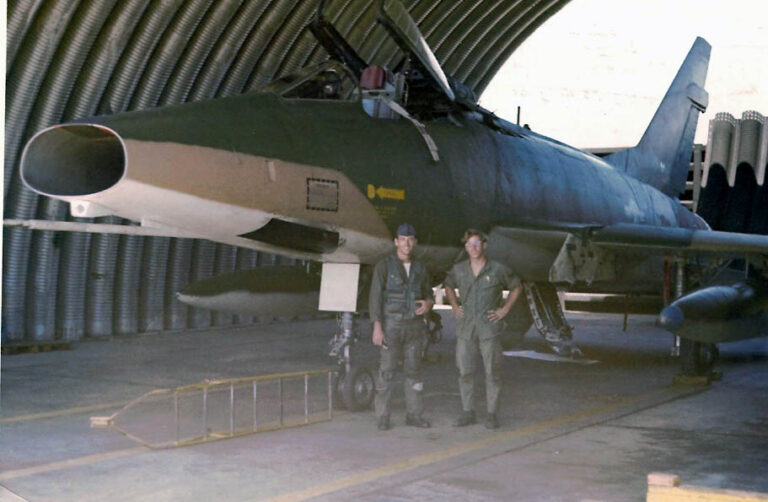 """This photo shows """"our"""" aircraft """"101"""" (56-3101) in the hangar. From left to right: The pilot (Captain Harry C. Brown) and me (Bob Guier) in front of 101. Note by Brushface: 56-3101, 612 Det 1, Phan Rang, RVN, survived to become QF 340 Target Drone and was destroyed on 5 November, 1991, Tyndall AFB. The covered revetments were not there when I left in August, 1968, so they were added after I left. We only had open air revetments. Apparently, since Charlie started using Phan Rang for target practice and dropping as much as they could, the wheels, decided that putting the aircraft in a covered area might be a good idea."""