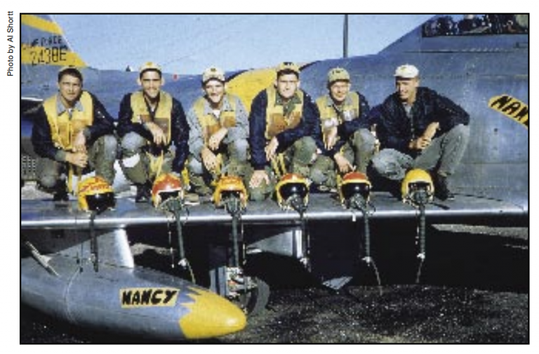"""members of the 80th FighterBomber Squadron, called the """"Headhunters,"""" are suited up and ready for another mission. Pictured (l-r) are: 2nd Lt. Vince Bakies, 2nd Lt. Bob Debenport, 2nd Lt. Al Shortt, 2nd Lt. Dick Wyatt, 2nd Lt. Ray Eason, and 1st Lt. Ken Dye. (From AF Magazine article Sabres and Aces)"""