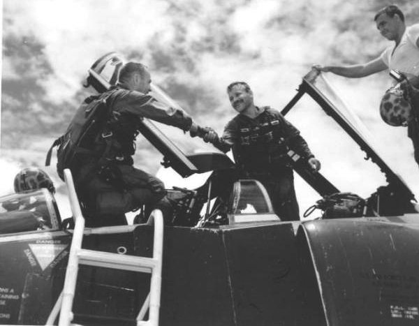 First Air Force F-4 Navigator Complete 100 Missions Over North – Southeast Asia – 'Put 'Er There, Partner' – that's what Major Ronald C. Herrick (left), 37, Houston, Texas, said when congratulating his back-seater, Captain Herbert Altman (center), 29, North Miami Beach, Florida, upon completion of his 300th combat mission over the Southern Panhandle of North Vietnam recently. Altman was the first F-4 Navigator to have completed 100 combat missions…